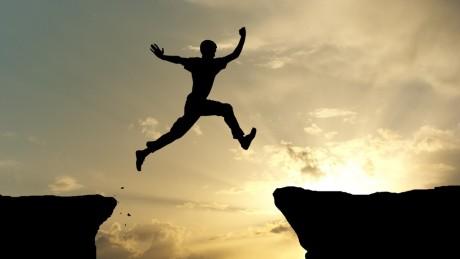 man-jumping-across-gap-between-rocks_1295540054